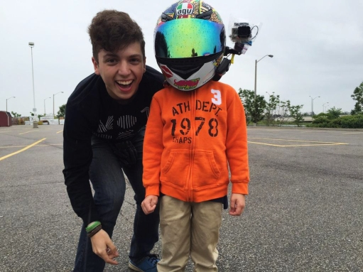 Cute kid next to DMotovlogs (Owner) wearing his helmet.